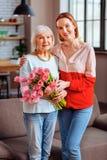Geschotene grijs-haired dame stellen het van gemiddelde lengte met dame in rozeachtige blouse royalty-vrije stock fotografie
