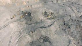 Geschotene panorama luchtmening, open kuilmijn, mijnbouw, kipwagens, uithakkend mijnbouw, die van het werk ontdoen stock videobeelden