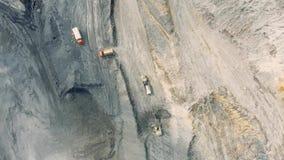 Geschotene panorama luchtmening, open kuilmijn, mijnbouw, kipwagens, uithakkend mijnbouw, die van het werk ontdoen stock video