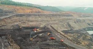Geschotene panorama luchtmening, open kuilmijn, mijnbouw, kipwagens, uithakkend mijnbouw, die van het werk ontdoen Mening van stock videobeelden
