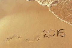 geschreven het jaar van 2016 en voetafdruk op zandige strandoverzees Stock Afbeelding