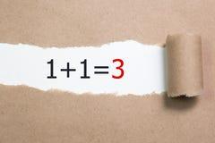 1+1=3 geschreven in het kader van gescheurd pakpapier Royalty-vrije Stock Foto