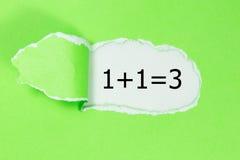 1+1=3 geschreven in het kader van gescheurd pakpapier Zaken, technologie Royalty-vrije Stock Afbeelding