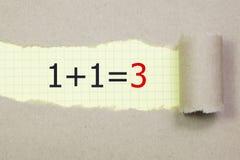 1+1=3 geschreven in het kader van gescheurd pakpapier Zaken, technologie, Internet-concept Stock Foto