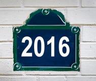 2016 geschreven op een de straatplaat van Parijs op een witte muur Stock Foto