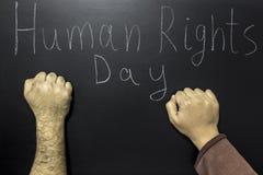 Geschreven tekst: Rechten van de mensdag met twee vuisten stock foto