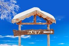 2017 geschrieben auf einen hölzernen Wegweiser, einen blauen Himmel und einen gefrorenen Baum Stockbild
