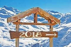 2018 geschrieben auf einen hölzernen Wegweiser, Schneeberglandschaft auf dem Hintergrund Lizenzfreie Stockfotografie