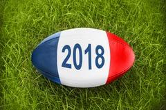 2018 geschrieben auf einen Rugbyball in das Gras, blaue weiße rote französische Flaggenfarben Lizenzfreie Stockfotos