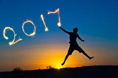 2017 geschrieben mit Scheinen, Schattenbild eines Jungen, der in die Sonne, Konzept des neuen Jahres springt Stockfotografie