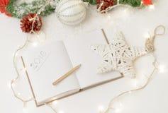 2016 geschrieben in Notizblock mit einem Dekor des Bleistifts, der Kerze und des neuen Jahres Lizenzfreie Stockfotos