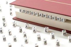 Geschriebene kyrillische Briefe des Gewinns des Wortes zerstreuen Fantasie zwischen Buchblättern und kyrillischen Buchstaben auf  Stockfotos