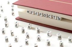 Geschriebene kyrillische Briefe des Gewinns des Wortes zerstreuen Klugheit zwischen Buchblättern und kyrillischen Buchstaben auf  Lizenzfreie Stockfotografie