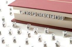 Geschriebene kyrillische Briefe des Gewinns des Wortes zerstreuen Kreativität zwischen Buchblättern und kyrillischen Buchstaben a Stockbilder