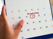 Geschriebener roter Kreis des Frauenhandgriffs weißer Kalender und Jahrestagswort markiert auf weißem Kalender Diese zu erinnern  stockbilder
