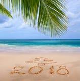 Geschriebenes und karibisches Meer der neues Jahr-Aufschrift 2018 mit grüner Palme Lizenzfreie Stockbilder