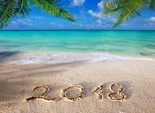 Geschriebenes und karibisches Meer der neues Jahr-Aufschrift 2018 mit grüner Palme Lizenzfreie Stockfotos