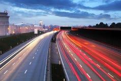 Geschwindigkeits-Verkehr am zeit- Licht des drastischen Sonnenuntergangs schleppt auf motorwa stockfotografie