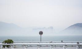 Geschwindigkeitsbeschränkungsbrett vor Meer Lizenzfreies Stockfoto