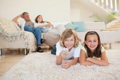 Geschwister auf dem Teppich fernsehend Stockfotos