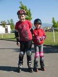 Geschwister auf rollerskates Stockfoto