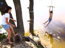 Geschwister Bruder und Schwester unterhalten sich mit Wasserschwingen im Urlaub Stockfotografie