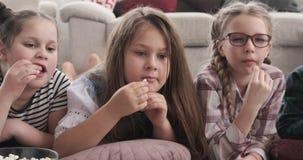 Geschwister, das Film aufpasst und Popcorn isst stock footage