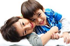Geschwister des kleinen Jungen, die zusammen liegen stockbild