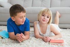 Geschwister, die auf das Bodenlesemärchenbuch legen Lizenzfreies Stockbild