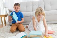 Geschwister, die auf dem Bodenlesemärchenbuch sitzen Lizenzfreies Stockfoto