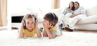 Geschwister, die auf dem Fußboden mit Kopfhörern spielen lizenzfreies stockbild