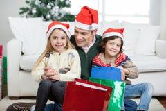 Geschwister, die auf Lap With Christmas des Vaters sitzen Lizenzfreie Stockfotografie