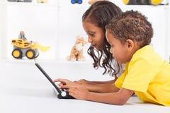 Geschwister, die Computer spielen Stockbilder