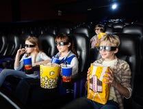 Geschwister, die Film 3D im Theater aufpassen Stockbilder