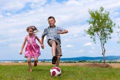 Geschwister, die Fußball im Garten spielen Stockbilder
