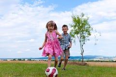 Geschwister, die Fußball im Garten spielen Lizenzfreies Stockbild