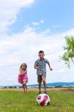 Geschwister, die Fußball im Garten spielen Lizenzfreie Stockbilder