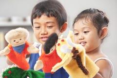 Geschwister, die Handmarionette spielen Stockfoto