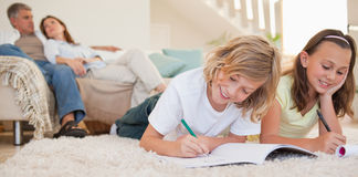 Geschwister, die ihre Heimarbeit auf dem Teppich tun Lizenzfreie Stockfotos