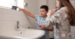Geschwister, die ihre Zähne putzen stock footage