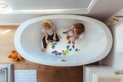 Geschwister, die innerhalb einer Badewanne spielen lizenzfreie stockfotografie