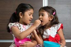 Geschwister, die Lebensmittel teilen Stockfotos