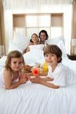 Geschwister, die mit ihren Muttergesellschaftn frühstücken Lizenzfreies Stockfoto