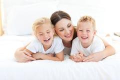 Geschwister, die mit ihrer Mutter liegt auf einem Bett spielen lizenzfreie stockbilder