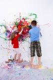 Geschwister, die zeitgenössische Kunst auf weißer Wand malen Stockbild