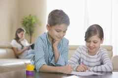 Geschwister, die zusammen bei Tisch mit Mutter im Hintergrund zeichnen Stockfoto