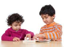 Geschwister, die zusammen ein Abbildung-Buch lesen Lizenzfreie Stockbilder