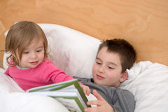 Geschwister, die zusammen lesen Stockbilder