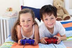 Geschwister, die zusammen Videospiele spielen Stockfotografie