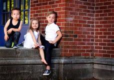 Geschwister durch Wand des roten Backsteins Lizenzfreie Stockfotos